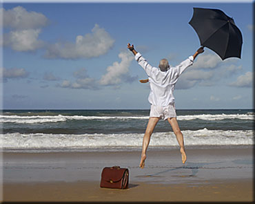 Business man jumping on beach